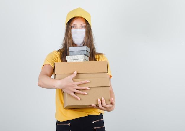 Donna di consegna che abbraccia scatole in t-shirt, pantaloni e berretto, maschera e sembra allegra