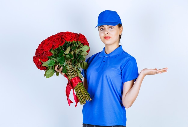 Delivery woman employee in blue uniform standing and holding bouquet of roses .