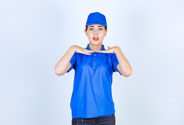 Delivery woman employee in blue uniform standing and posing.