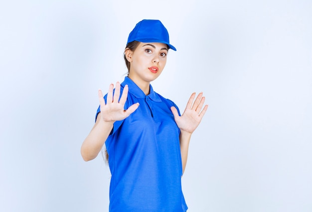Delivery woman employee in blue uniform standing and showing stop sign .