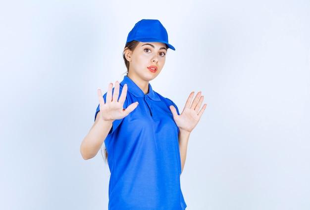 파란색 유니폼을 입고 서서 정지 신호를 보여주는 배달 여성 직원.