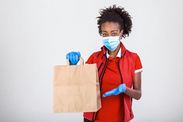 赤いtシャツの制服マスクグローブの配達女性従業員は、食品とクラフト紙袋を保持します