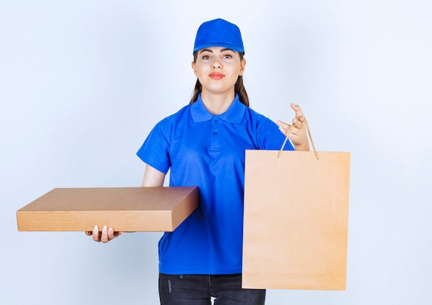 Delivery woman employee in uniform holding craft paper box with bag.