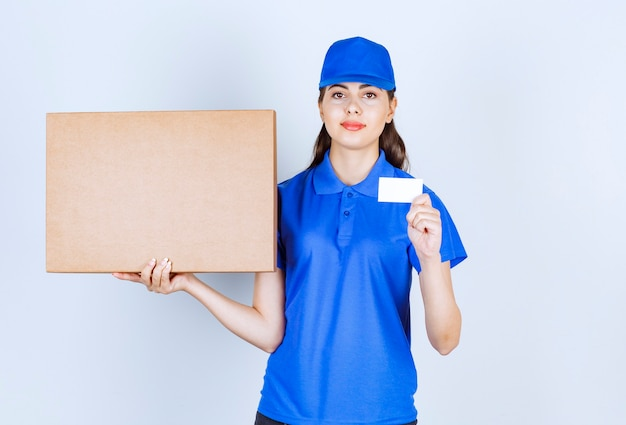 Delivery woman employee in uniform holding craft paper box with card .