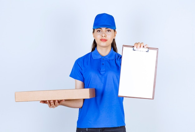 Delivery woman employee in uniform holding craft paper box with folder .