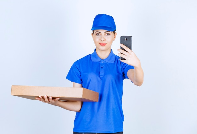 Delivery woman employee in uniform holding craft paper box with mobile phone .