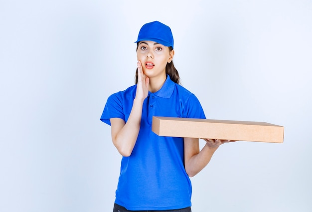Delivery woman employee in uniform holding craft paper box .