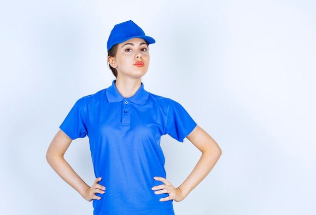 Delivery woman employee in uniform standing and posing with hands oh hips.