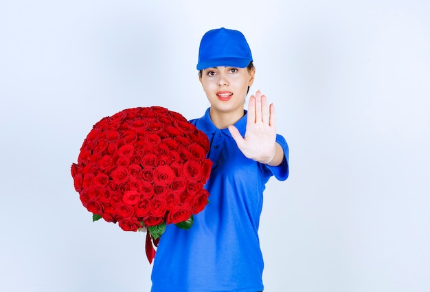 Delivery woman employee in uniform with bouquet of roses showing stop sign.