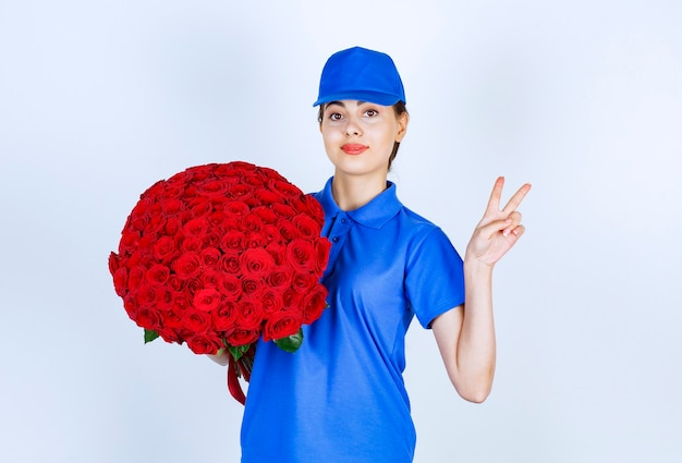 Delivery woman employee in uniform with bouquet of roses showing victory sign .