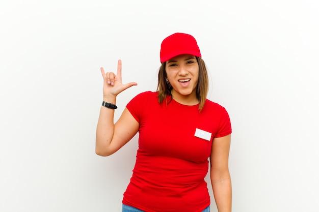 Доставка женщина чувствует себя счастливым, веселым, уверенным, позитивным и мятежным, делая знак рок или хэви-метал рукой на белом