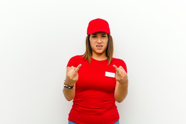 Delivery woman feeling provocative, aggressive and obscene, flipping the middle finger, with a rebellious attitude