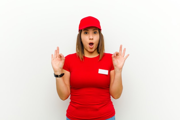Delivery woman feeling shocked, amazed and surprised, showing approval making okay sign with both hands