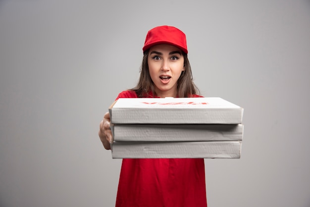 Delivery woman giving away from pizza orders.