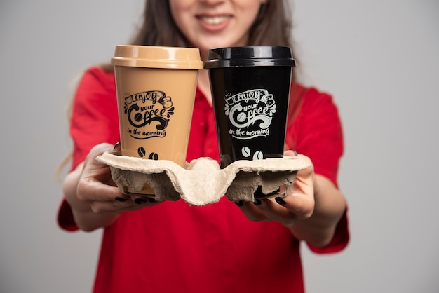 Delivery woman giving coffee cups on gray wall.