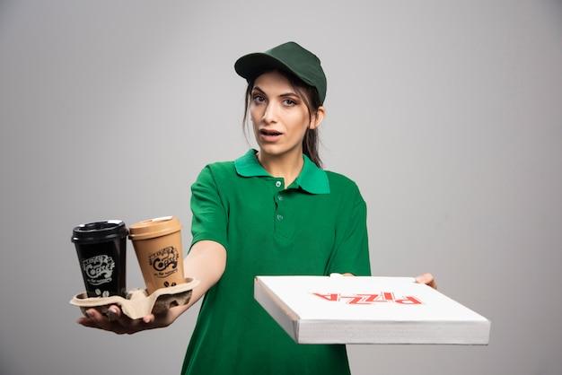 Donna di consegna che dà la scatola della pizza al cliente