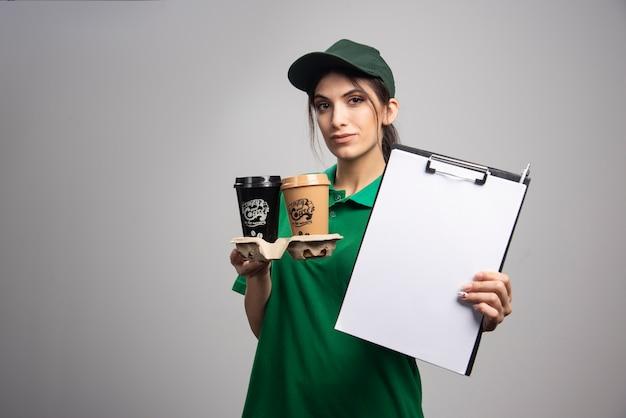 Donna di consegna in verde che mostra appunti.
