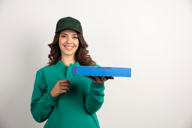 Donna delle consegne in uniforme verde che tiene la scatola della pizza.