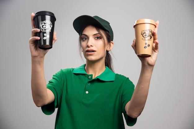 Donna di consegna in uniforme verde in posa con tazze di caffè