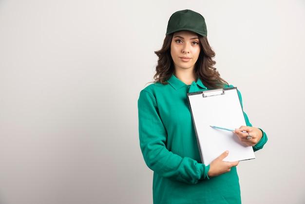 Donna delle consegne in uniforme verde che mostra i dettagli dell'ordine.