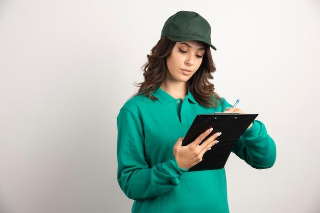 Donna delle consegne in uniforme verde che scrive i dettagli dell'ordine.