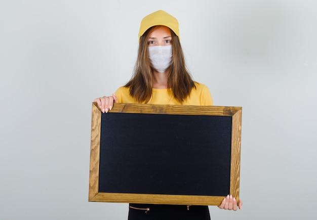 Tシャツ、ズボン、キャップ、マスクで黒板を保持している配達の女性