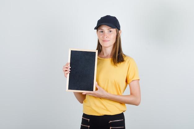 Donna di consegna tenendo la lavagna in t-shirt, pantaloni e berretto e guardando felice