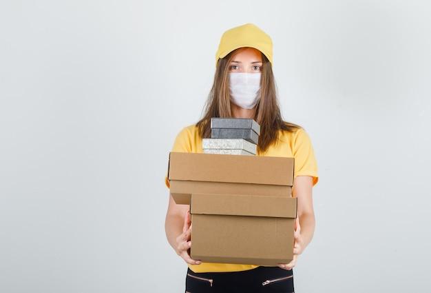 Donna di consegna che tiene scatole in t-shirt, pantaloni e berretto, maschera e sembra allegro
