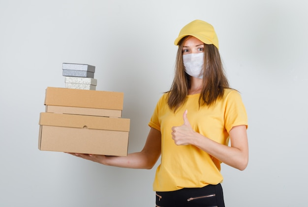 Delivery woman holding boxes with thumb up in t-shirt, pants and cap, mask and looking cheery