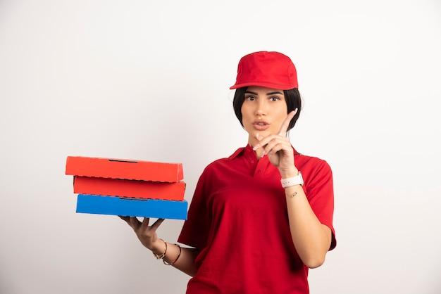 Женщина доставки, держащая кучу коробок для пиццы.