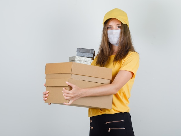 Доставщица держит картон и подарочные коробки в футболке, штанах и кепке, маске и выглядит весело