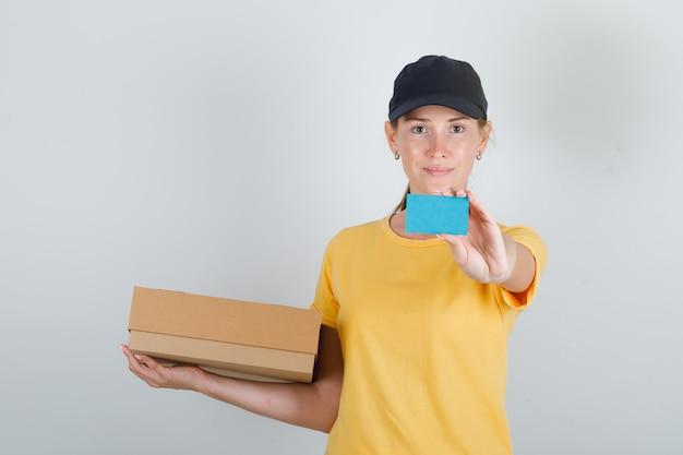 Женщина-доставщик, держащая картонную коробку и синюю карточку в футболке и кепке