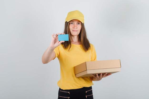 Доставщица держит картонную коробку и синюю карточку в футболке, штанах и кепке и выглядит радостной