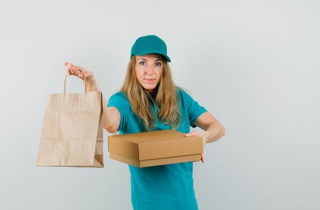 Женщина-доставщик, держащая картонную коробку и бумажный пакет в футболке, крышке и выглядящая жизнерадостной.