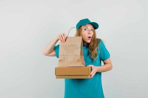 Женщина-доставщик, держащая картонную коробку и бумажный пакет в футболке, кепке и любопытно глядя.