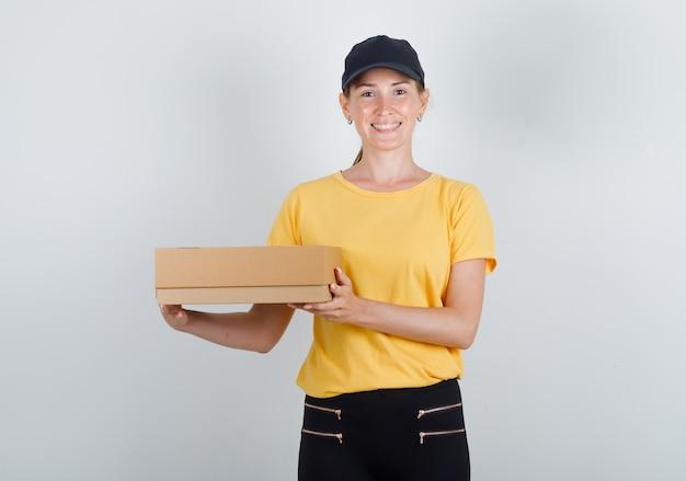 Доставщик женщина держит картонную коробку и улыбается в футболке, штанах и кепке