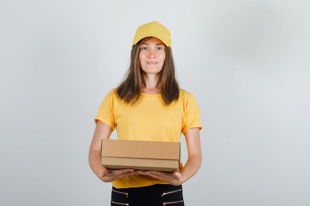 Доставщица держит картонную коробку и улыбается в желтой футболке, штанах и кепке