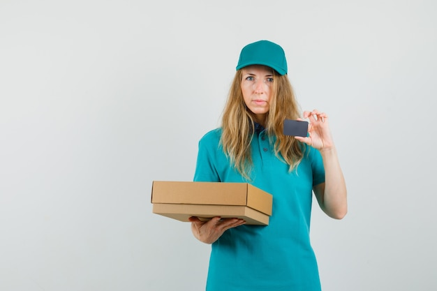 Delivery woman holding cardboard box and card in t-shirt, cap