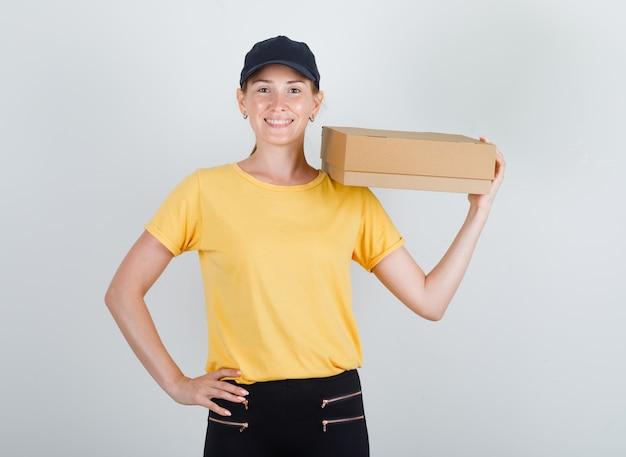 Donna di consegna tenendo la scatola di cartone sulla sua spalla in t-shirt, pantaloni e berretto