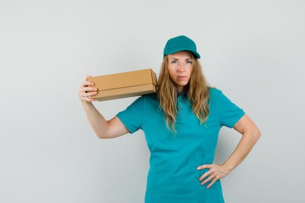 Доставщица держит картонную коробку в футболке, кепке и выглядит уверенно