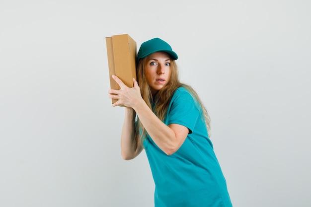 Donna di consegna che tiene la scatola di cartone vicino al suo orecchio in t-shirt, berretto e guardando curioso.