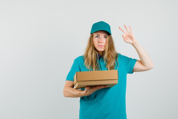 Delivery woman holding cardboard box and showing ok sign in t-shirt, cap