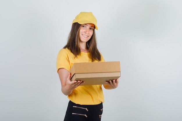 Donna di consegna che tiene la scatola di cartone e sorridente in maglietta, pantaloni e cappuccio gialli