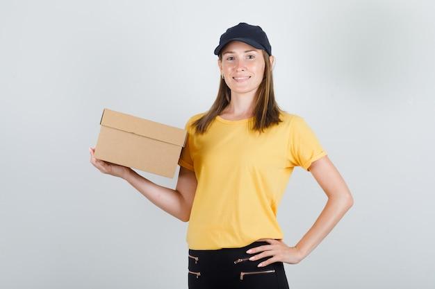 Donna di consegna che tiene la scatola di cartone in t-shirt, pantaloni e berretto e sembra allegra