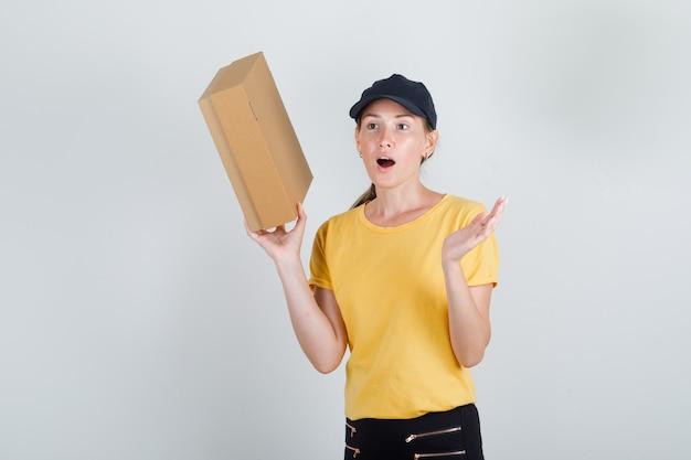 Donna di consegna tenendo la scatola di cartone in t-shirt, pantaloni e berretto e guardando sorpreso