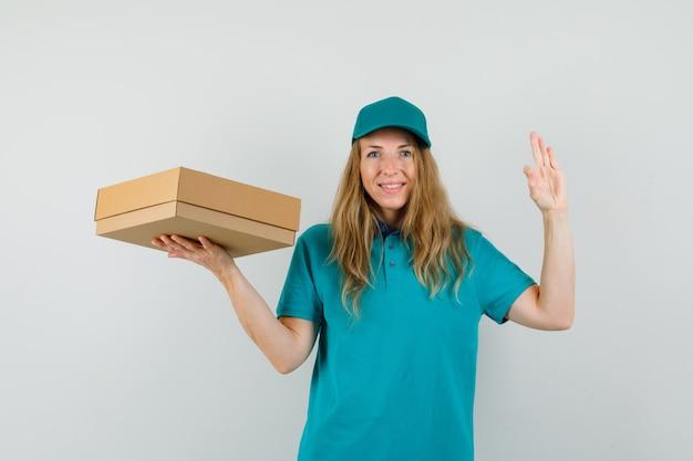 Tシャツ、キャップ、okのジェスチャーで段ボール箱を押しながら陽気な配達の女性
