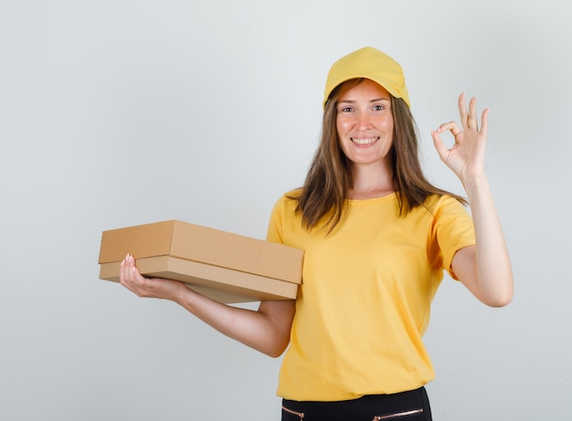 Delivery woman holding cardboard box with ok sign in yellow t-shirt, pants and cap and looking glad