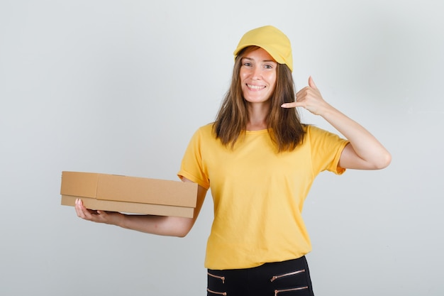 Delivery woman holding cardboard box with phone sign in yellow t-shirt, pants and cap and looking glad