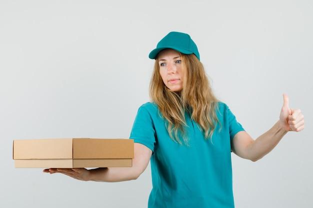 Donna di consegna che tiene la scatola di cartone con il pollice in su in t-shirt, berretto