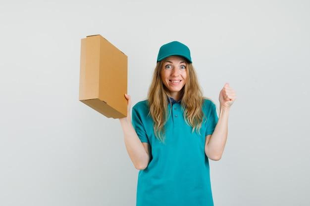 Donna di consegna che tiene la scatola di cartone con il gesto del vincitore in t-shirt, berretto e che sembra felice